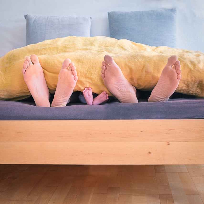 family of three lying on bed showing feet while covered with yellow blanket